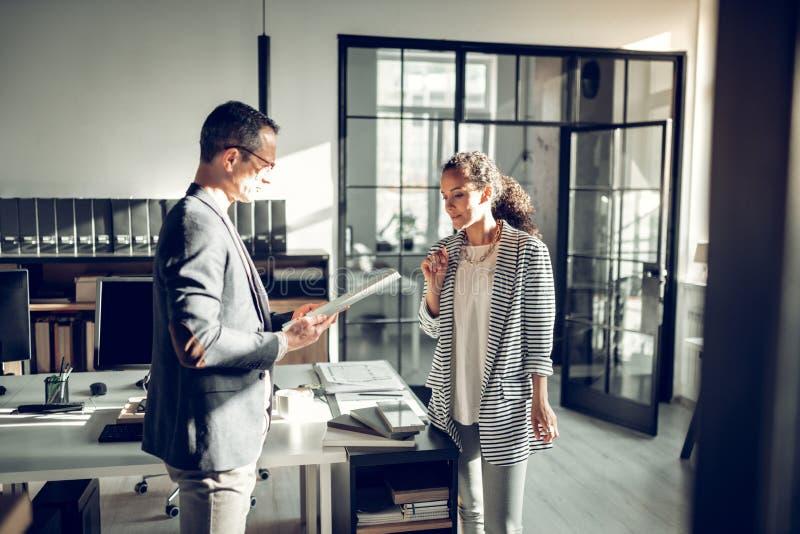 Полезная секретарша принося некоторые документы для ее занятого босса стоковые фотографии rf