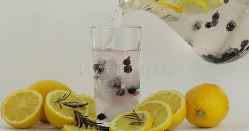 Полейте в стекло холодный напиток Лимон, лед и черная смородина в стекле напитка стоковые изображения rf