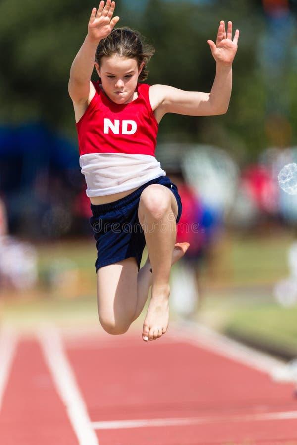 Полет девушки большого скачка атлетики стоковые фотографии rf