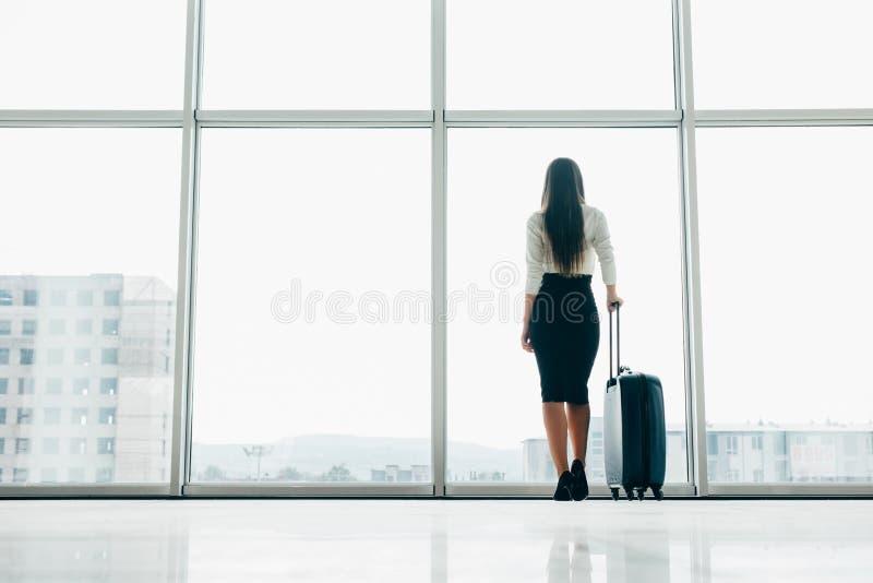Полет коммерсантки путешественника ждать задержанный на салон авиапорта стоя с гудронированным шоссе багажа наблюдая на окне авиа стоковые фотографии rf