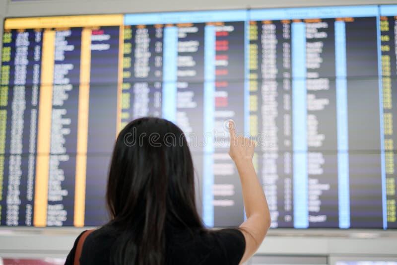 Полет путешественника женщины проверяя отклонения всходит на борт на airpor стоковое изображение
