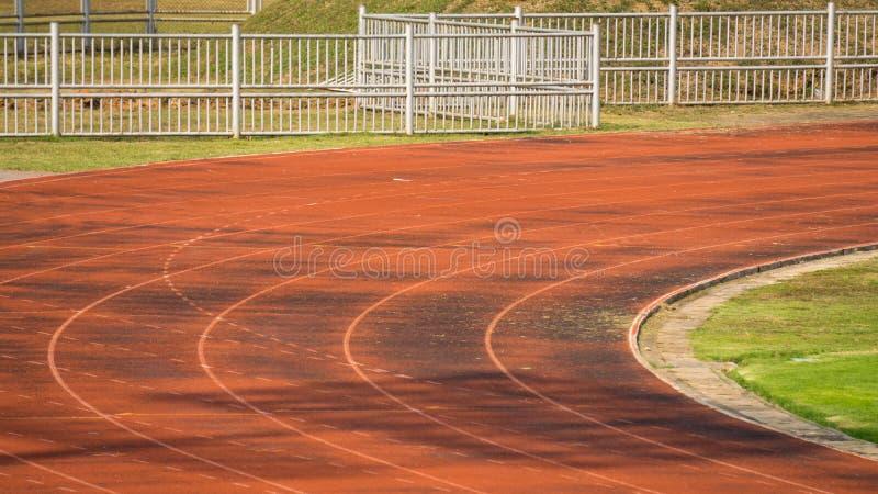 Поле старой атлетической беговой дорожки и зеленой травы в футбольном стадионе стоковые фото