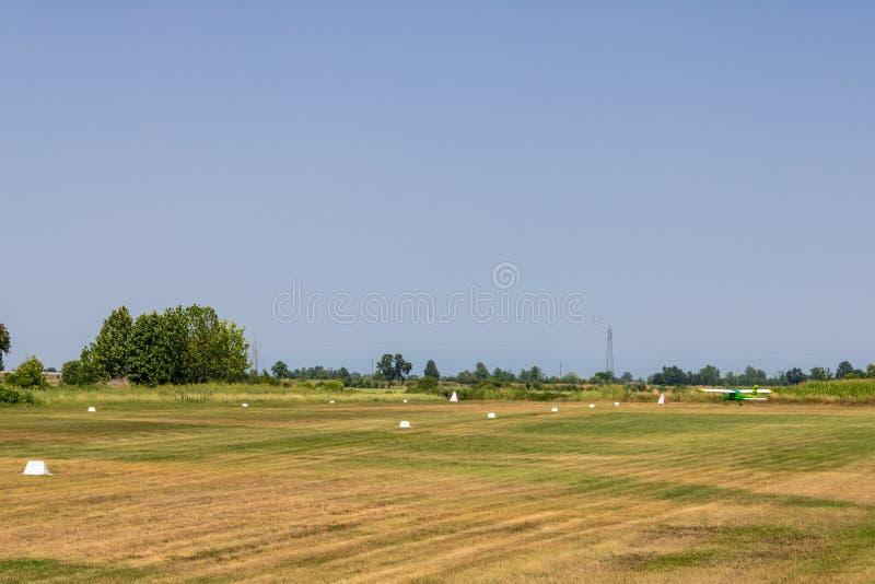 Поле с взлетно-посадочной дорожкой и небольшими воздушными судн, взлетно-посадочной дорожкой поля травы - изображением стоковые фотографии rf