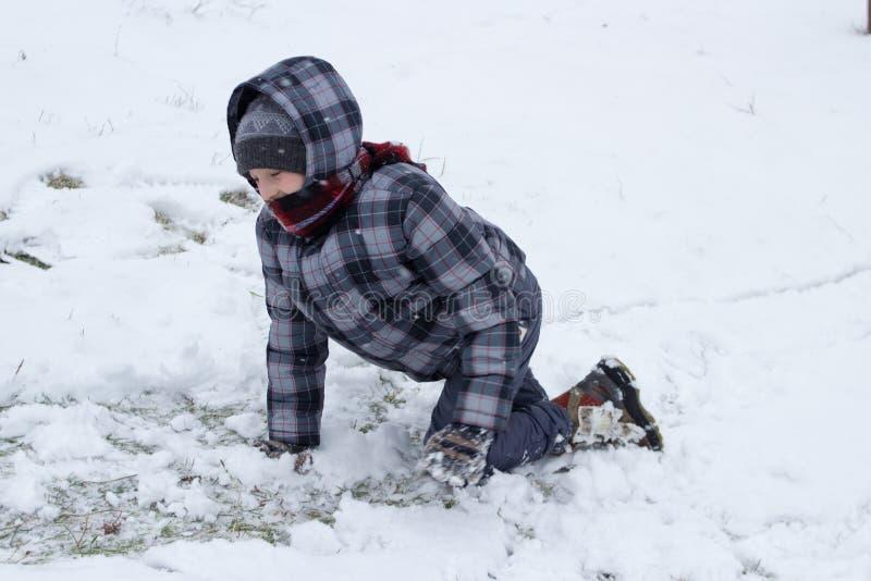 Ползания мальчика в снеге стоковая фотография