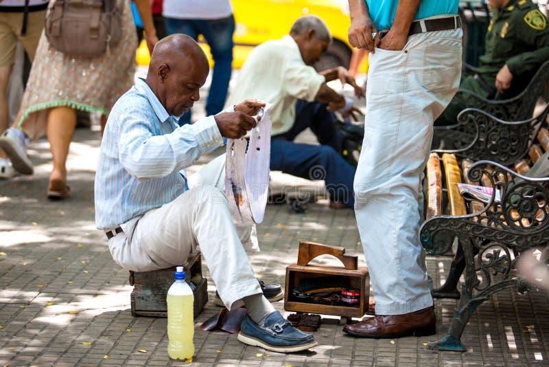 Полировщик ботинка улицы на квадрате Bolivar в огороженном городе Cartagena de Indias стоковое изображение rf