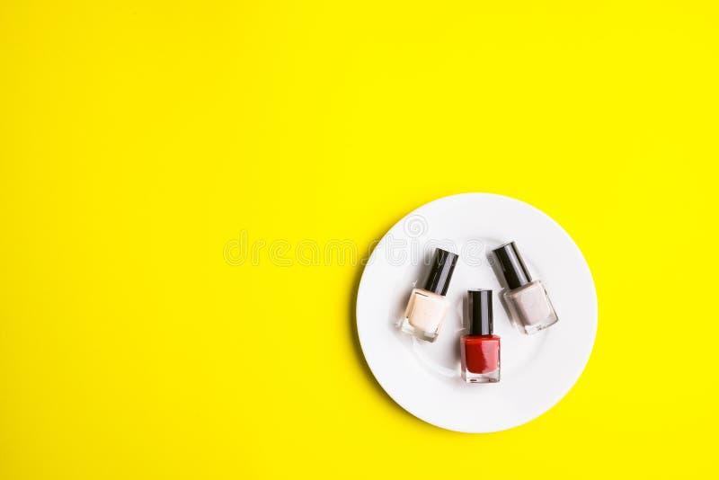 Полировщик ногтя на белом блюде на желтой предпосылке, концепции косметик, концепции макияжа, изображении для вашего текста, Fla  стоковая фотография rf