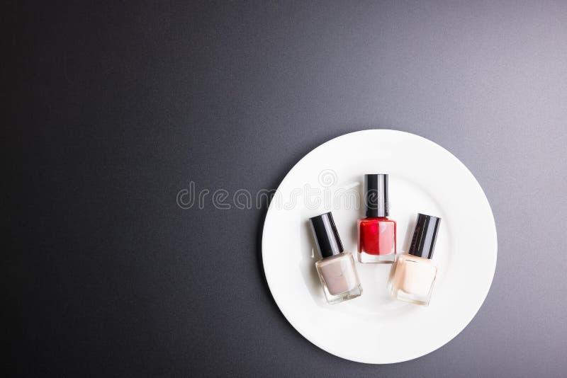 Полировщик ногтя на белом блюде на черной предпосылке, концепции косметик, концепции макияжа, изображении космоса экземпляра для  стоковое фото