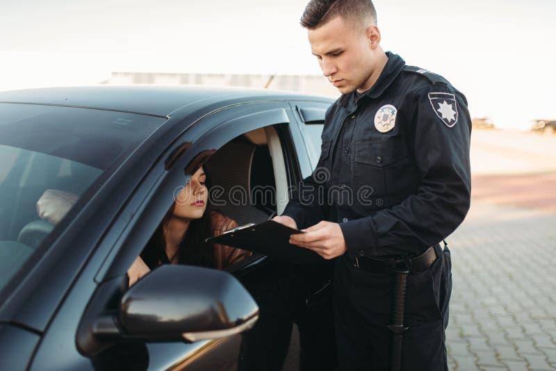 Полисмен в форме проверяет лицензию женского водителя стоковое изображение