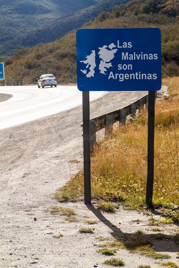 Политический знак обочины около государств Ushuaia: Сын Argetinas Falklands Мальвинских островов Las принадлежит Argentin стоковое фото rf