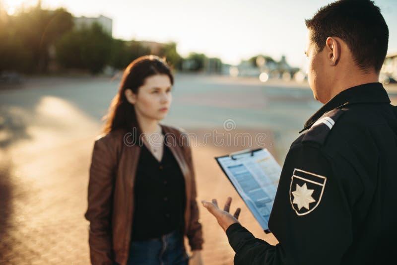 Полицейские читают закон к женскому водителю стоковые фото