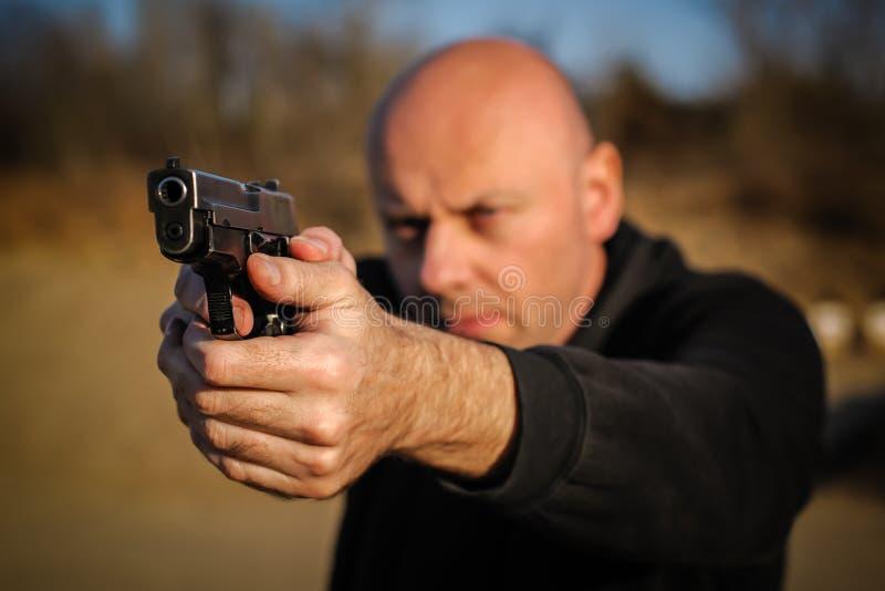 Полицейский агент и телохранитель указывая пистолет для защиты от атакующего стоковая фотография rf