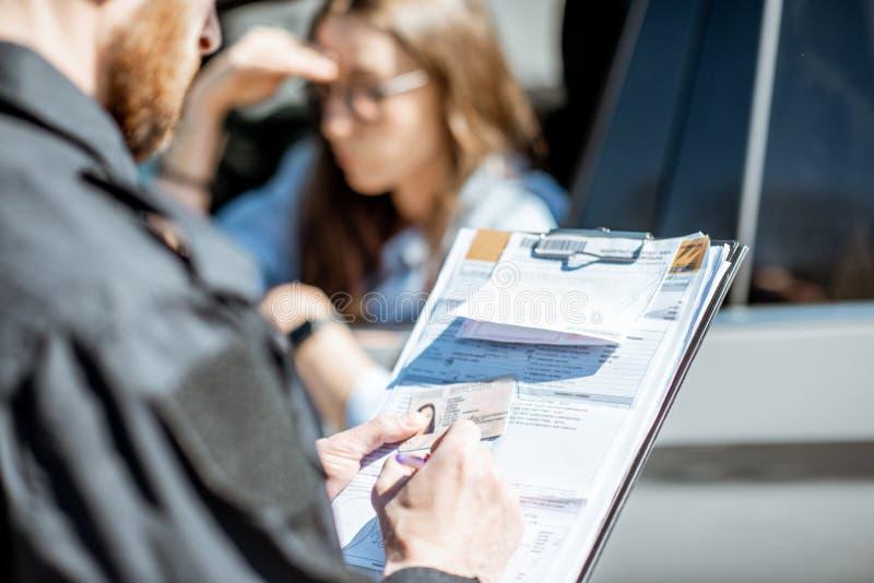 Полицейский выдавая штраф для женского водителя стоковые изображения rf