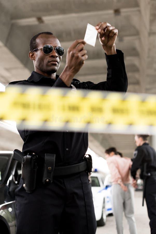полицейский в солнечных очках держа пластиковую молнию с лекарствами пока его партнер арестовывая женщину стоковые фото