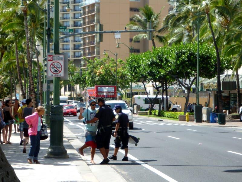 2 полиции Гонолулу bust человек для skateboarding в Waikiki стоковая фотография rf