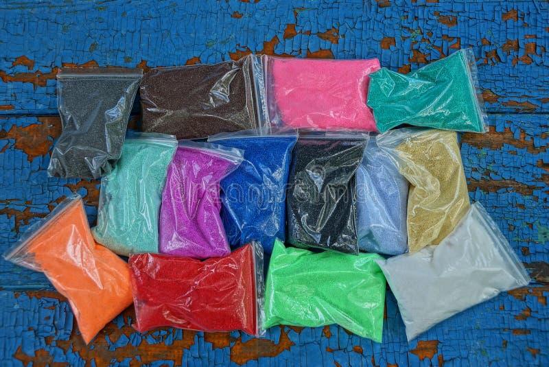 Полиэтиленовые пакеты с покрашенным песком на голубой таблице стоковые изображения rf