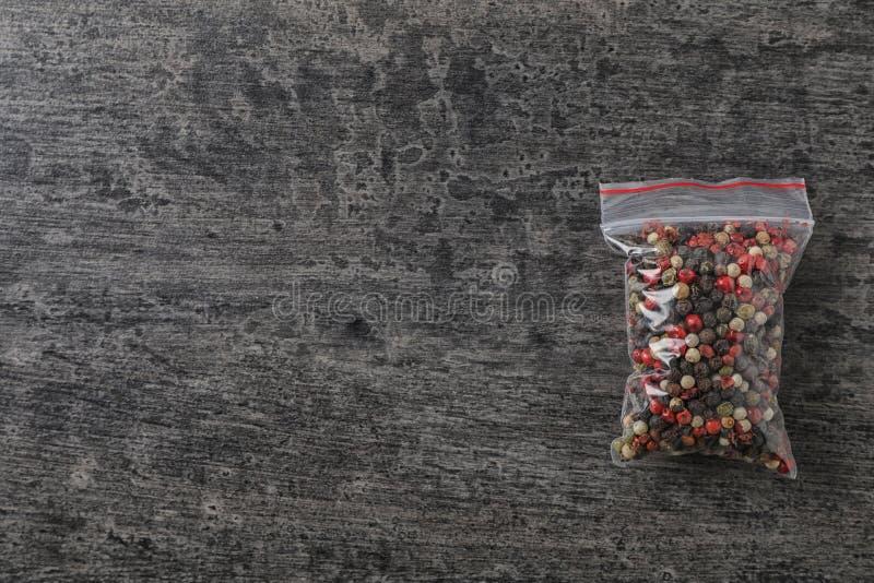 Полиэтиленовый пакет с специей на серой предпосылке, стоковое изображение rf