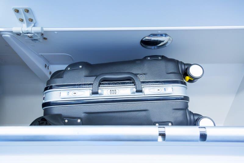Полка багажа с чемоданом багажа в самолете Интерьер воздушных судн перемещение карты dublin принципиальной схемы города автомобил стоковая фотография rf