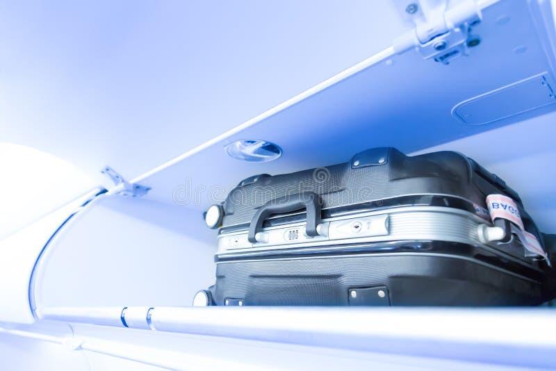 Полка багажа с чемоданом багажа в самолете Интерьер воздушных судн перемещение карты dublin принципиальной схемы города автомобил стоковая фотография