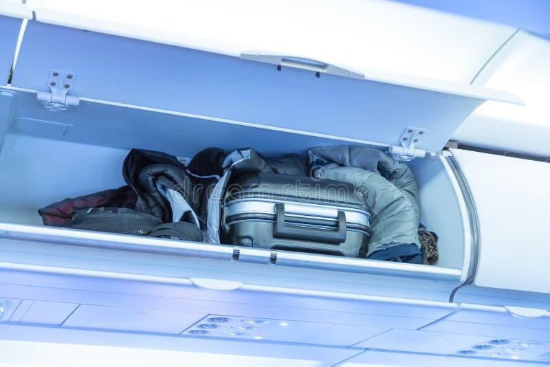 Полка багажа с чемоданом багажа в самолете Интерьер воздушных судн перемещение карты dublin принципиальной схемы города автомобил стоковое фото rf