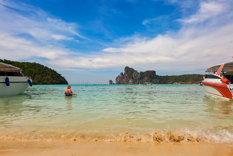 Полная женщина в купальном костюме приходит в море для плавать Взгляд на островах Phi Phi, песчаном пляже с волнами и сини стоковые фото