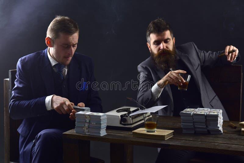 Полная концентрация на работе Бизнесмены считая деньги наличных денег Деловые партнеры писать финансовый отчет делать дела стоковое изображение rf
