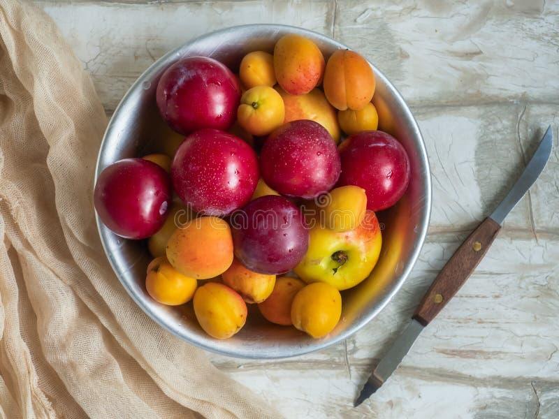 Полная плита зрелых свежих плода абрикоса, нектарина и конца-вверх на светлом деревянном столе, взгляда сверху сливы Нож с деревя стоковое фото rf