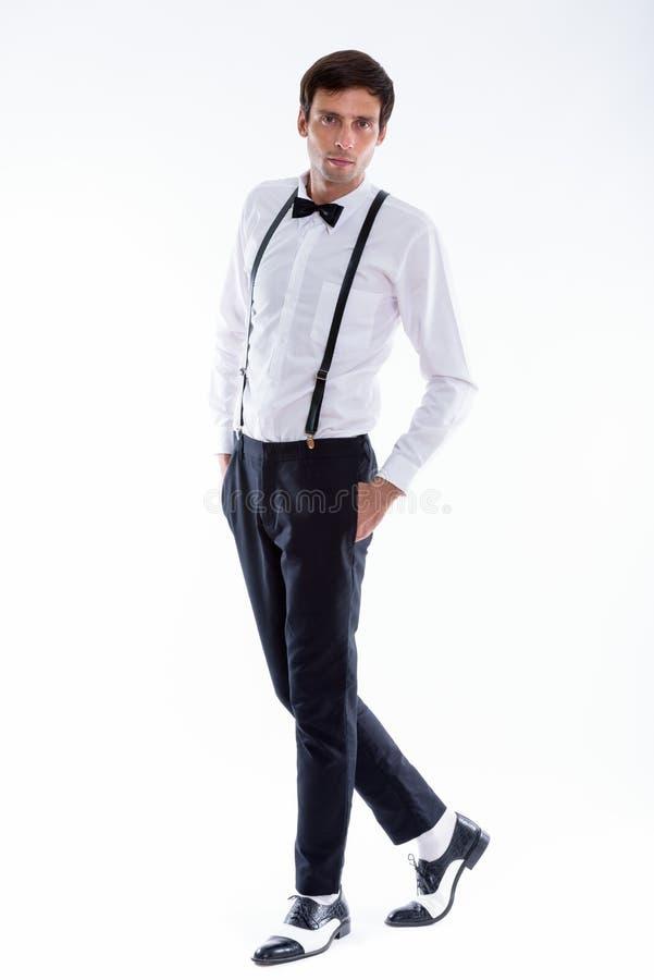 Полная съемка тела подтяжок и смычка молодого красивого человека нося стоковые фото