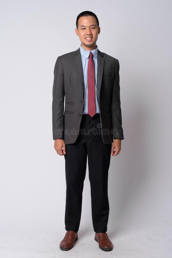 Полная съемка тела счастливого молодого азиатского бизнесмена в костюме стоковое изображение