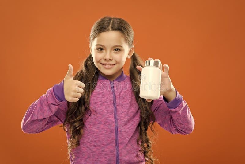 Полная формула поливитамина и минерального детища Принимать витамины Девушка держит бутылку с лекарствами Витамин стоковое фото