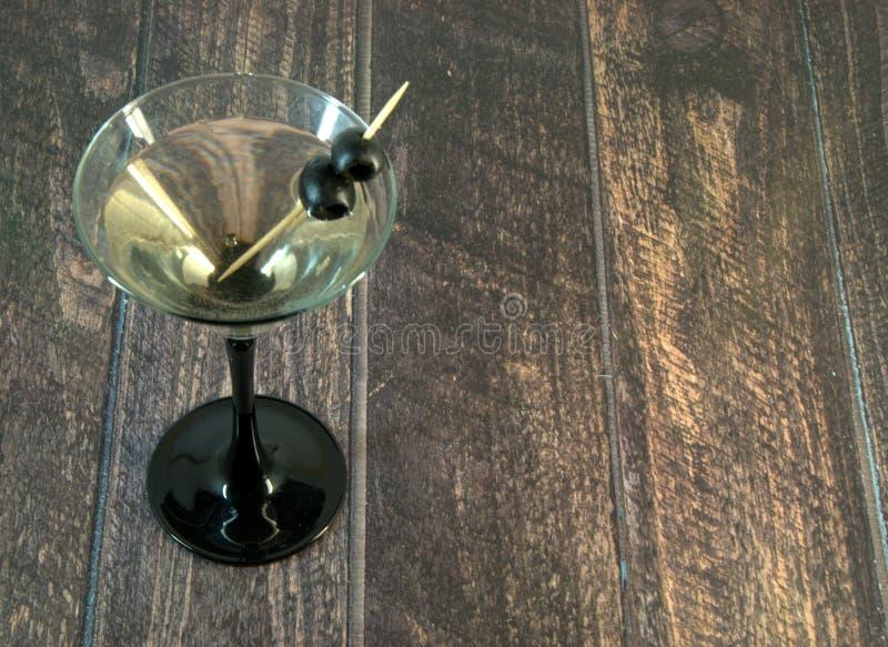 Полное стекло Мартини с 2 оливками на зубочистке стоит на деревянном столе стоковое изображение