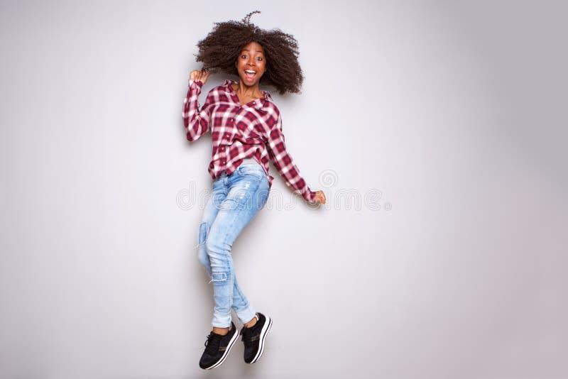 Полное тело возбудило молодую чернокожую женщину скача с утехой над белой предпосылкой стоковая фотография