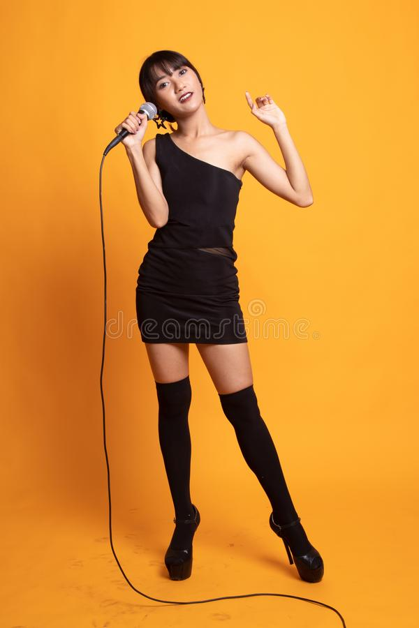 Полное тело красивой молодой азиатской певицы женщины поет с микрофоном стоковая фотография rf