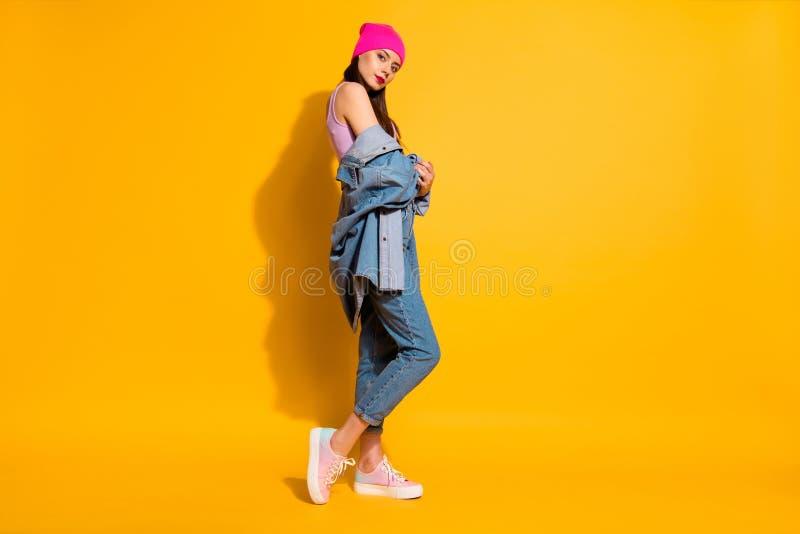 Полное фото взгляда низкого угла размера тела lngth сконцентрированной дамы держит джинсы джинсовой ткани руки покрывает симпатич стоковое фото