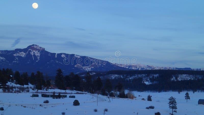 Полнолуние над горами в зиме стоковые изображения