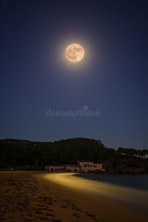 Полнолуние над испанским пляжем, около малого курортного поселка стоковая фотография rf