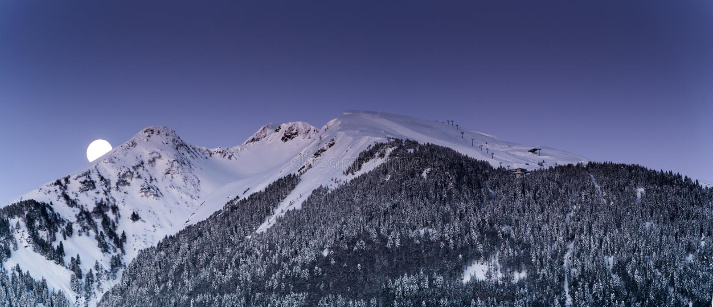 Полнолуние над ландшафтом горы зимы с подъемом лыжи на рассвет стоковое изображение rf