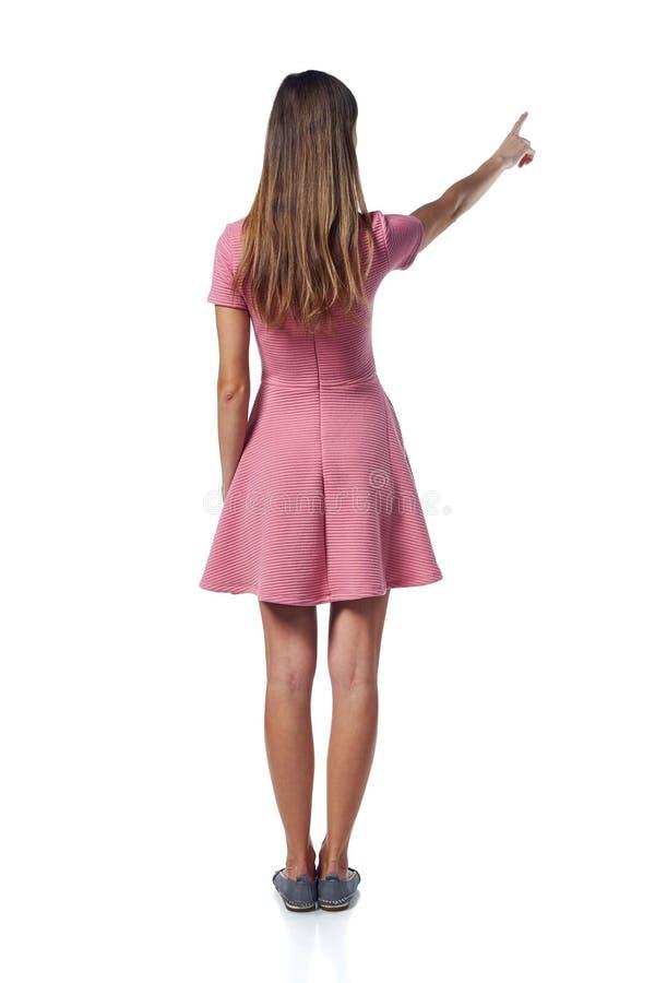 Полнометражная женщина в розовом платье указывая на сторону, задний взгляд стоковое фото rf