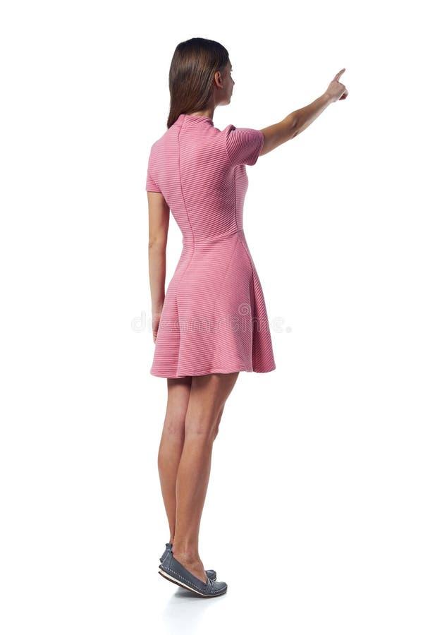 Полнометражная женщина в розовом платье указывая на сторону, задний взгляд стоковые изображения