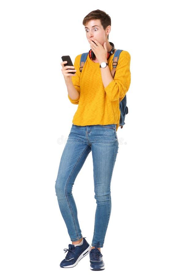 Полнометражная молодая женщина смотря мобильный телефон с удивленным выражением стоковые изображения rf