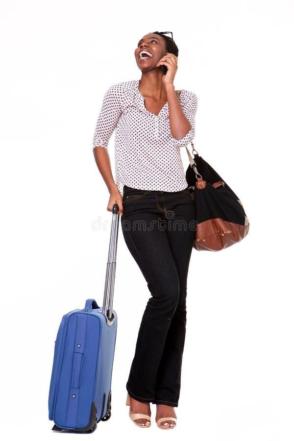 Полнометражная счастливая женщина стоя с чемоданом и умным телефоном на изолированной белой предпосылке стоковые фотографии rf