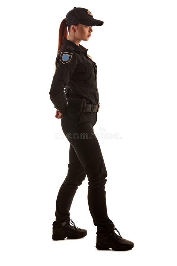 Полнометражная съемка redheaded женского полицейского представляя для камеры изолированной на белой предпосылке стоковое фото rf