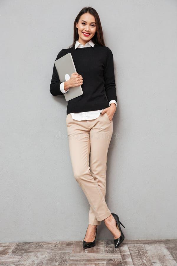 Полнометражное изображение довольной азиатской женщины в деле одевает стоковые изображения