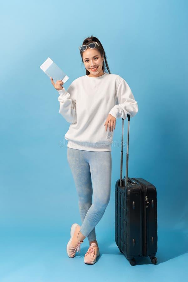 Полнометражное изображение жизнерадостной женщины нося в случайной одежде подготавливая задействовать с багажем и билетами над го стоковые изображения rf