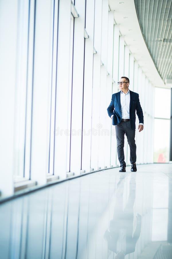 Полнометражное изображение среднего постаретого бизнесмена идя к камере и усмехаясь в офисном здании стоковое изображение rf