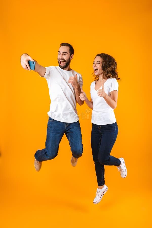 Полнометражное фото довольных пар смеясь и принимая selfie на смартфоне, изолированное над желтой предпосылкой стоковая фотография