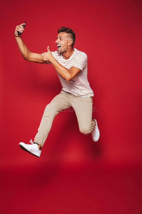 Полнометражное фото красивого человека в striped футболке скача и стоковое фото rf