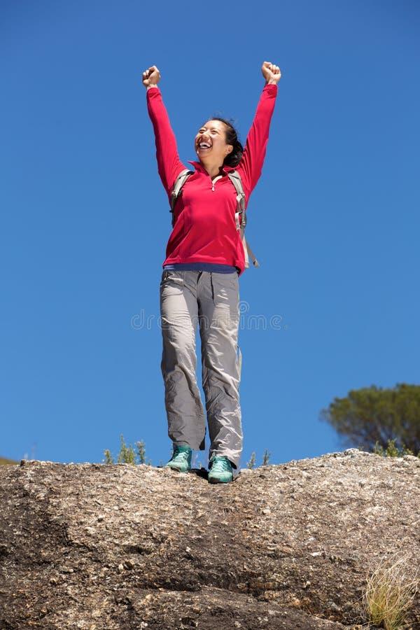 Полнометражный азиатский женский hiker стоя outdoors при поднятые руки стоковые фотографии rf