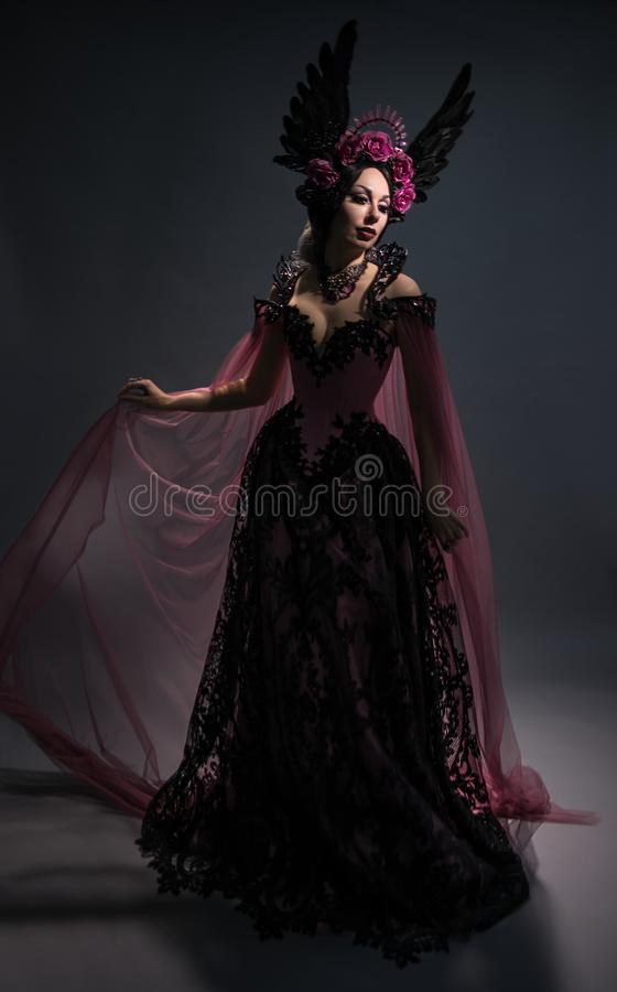 Полнометражный взгляд очаровательной женщины брюнет в розовой кроне стоковые изображения