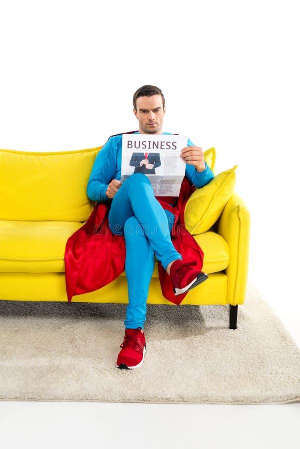 полнометражный взгляд серьезного мужского супергероя сидя на кресле и читая деловую газету стоковое фото rf