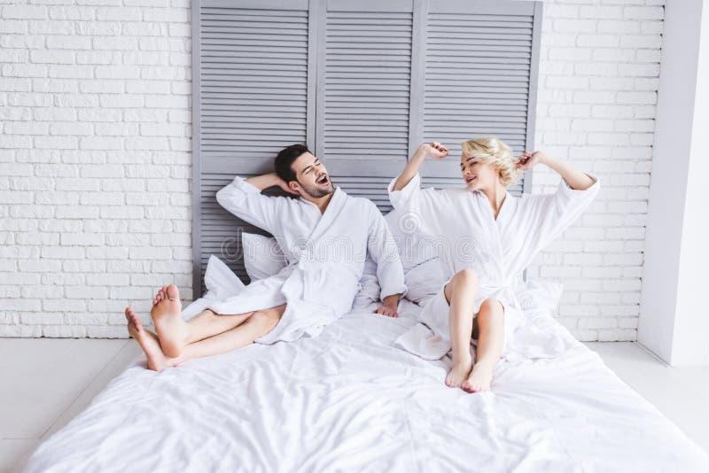 полнометражный взгляд счастливых молодых пар в купальных халатах протягивая на утре стоковые изображения